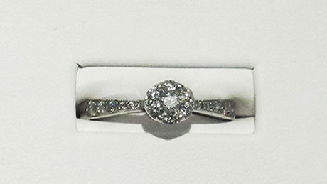 14 carat white gold ladies ring, 7 diamond ring on top, with small round brilliant diamonds along the sides.